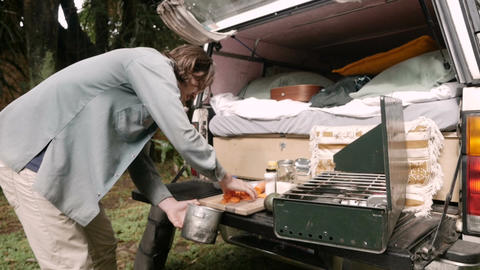 Handsome young man putting food into a camp pot to cook while camping in slow Live Action
