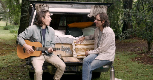 Two men with long hair and a guitar talking and sitting on a tailgate of a Footage