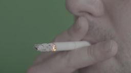 Smoking cigarettes in the smoker's mouth on a green background (close-up) Footage