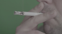 Smoking cigarette on green background (close-up) Footage