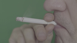 The smoker smokes a cigarette on a green background (close-up) Footage