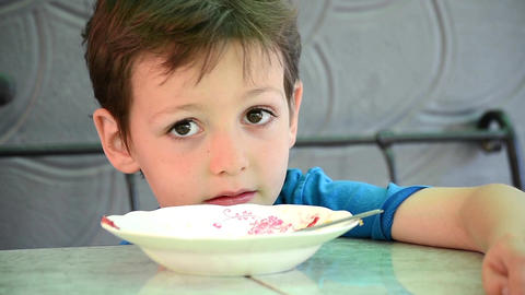 Early age boy sitting at the table next to empty plate and is glad that finished Footage