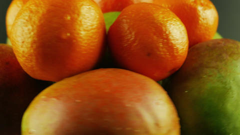 Macro Shot of Rotating Mangoes and Tangerines - Black Background Footage