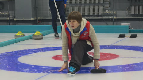 Girl curlers rolls a curling stone Footage