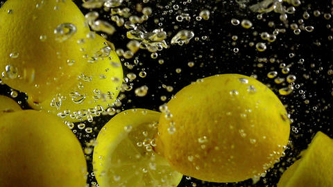 Whole and Sectioned Lemons Being Splashed into Water in Ultra Slowmotion Footage