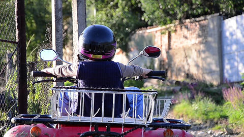 Child with black helmet in the head sitting on an ATV and mimicking as he leads  Footage