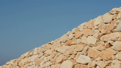 A fragment of a yellow stone wall on a blue sky background Image