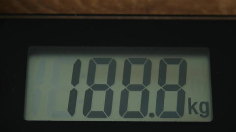 Bathroom digital scale close up with digits running up 画像
