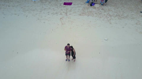 Boy and girl on the beach ocean. Aerial view. Bali Footage