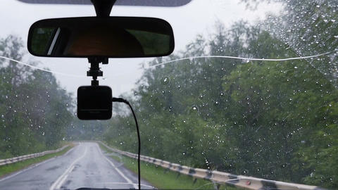 Drop of rain falls on the windshield of the car Footage