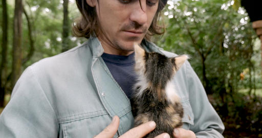 Intimate moment of a man in his 20s or 30s gently petting a young kitten while Footage