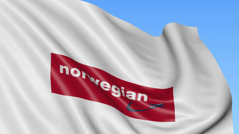 Waving flag of Norwegian Air Shuttle against blue sky background, seamless loop Footage