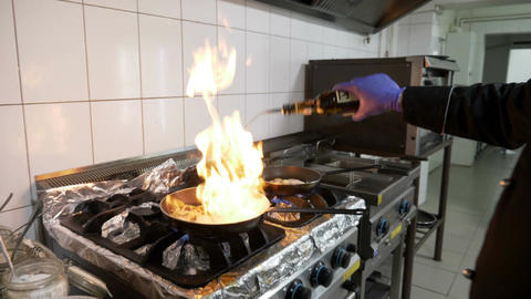 Professional male cook in restaurant kitchen flaming vegetables in pan using Footage