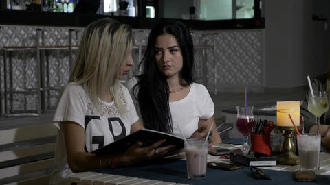 Two young beautiful girls in club sitting at a restaurant table trying to decide Footage