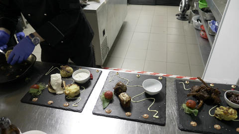 Male chef preparing three dishes in the kitchen of restaurant garnishing and Footage