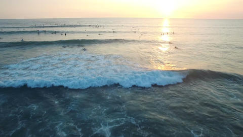 Flying over ocean with lots of surfers waiting in the water to the sunset Footage