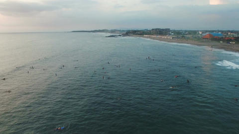 Flying above Surfers In Ocean Waiting For The Big Wave In the Evening Footage