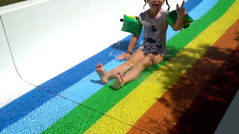 A child slides down a water slide. the second part Live Action