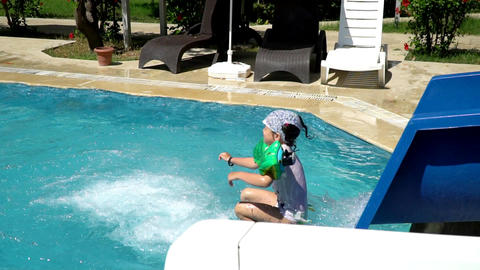 A child slides down a water slide into the pool. the third part Live Action