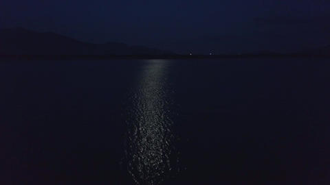Drone Flies over Moon Reflection on Lake Surface at Night Footage