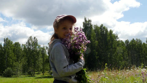 Little girl is standing with flowers in her hands and sniffing them Footage