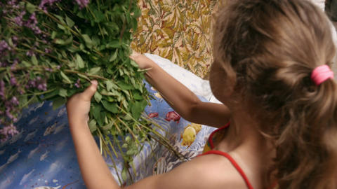 Little girl takes a bouquet of herbs and says something Footage