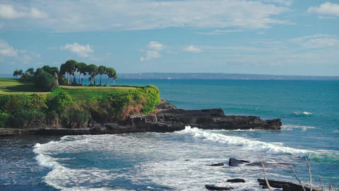 Bali landscape with ocean waves and rocky ledge with trees ビデオ