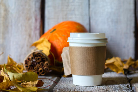 Autumn background with dry leaves and hot paper cup of coffee on wooden table Fotografía