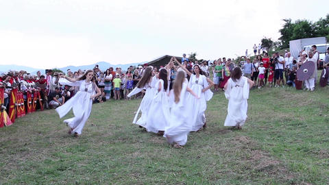 Group of women dressed in white dresses dancing at a medieval festival 60 Footage