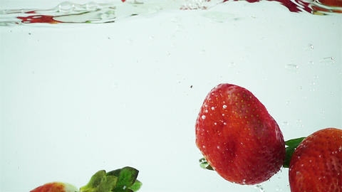 Ultra Slowmo Three Strawberries Splashed into Water on White Background Footage