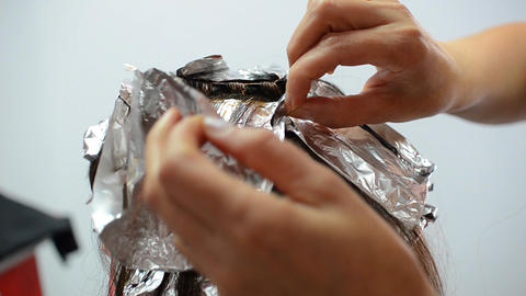Hairdresser packs strands of hair painted in tinfoil 10 Footage