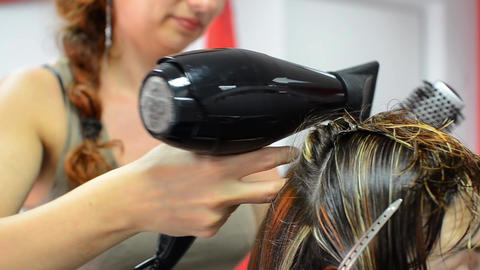 Hairdresser which dries with a hairdryer colored hair in strands of his client t Footage