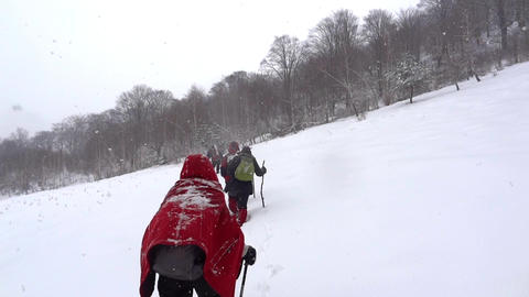 Hikers with backpack climb a slope with snow while doing a trip to the mountains Footage