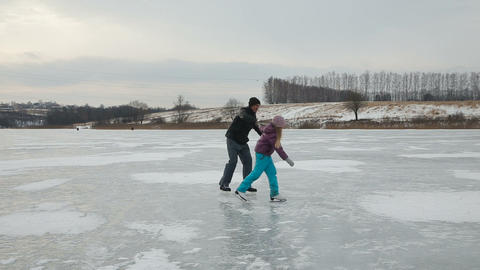 Father with daughter ice skating on frozen lake Footage