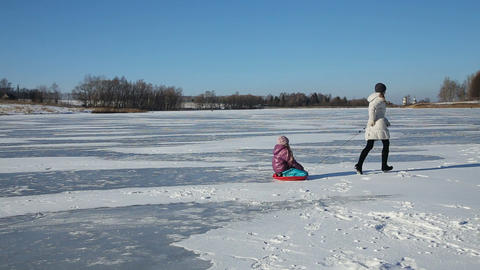 Mother and daughter sledding on frozen lake Footage