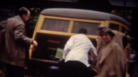 1943: Family packing woody station wagon car trunk for vacation trip Footage