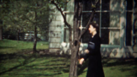1942: Women in black skirt suit walking from home in spring blossoms Footage