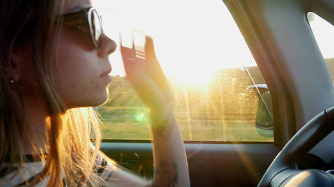Girl goes behind the wheel and puts on sunglasses Filmmaterial