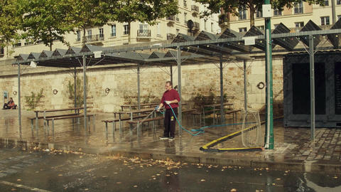 PARIS, FRANCE - OCTOBER 8, 2017. Man cleaning up fallen leaves on street cafe ライブ動画