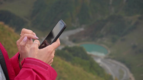 A Young Lady Using a Mobile Phone in Mountains Footage
