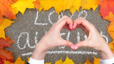 Woman hold hands in shape of heart against chalk written 'love autumn' Live Action