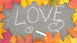 Chalk written LOVE word and two hearts on asphalt, colourful maple leaves around Live Action