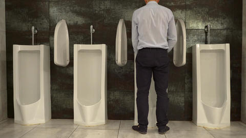 Man Peeing to Urinal in the Restroom Footage