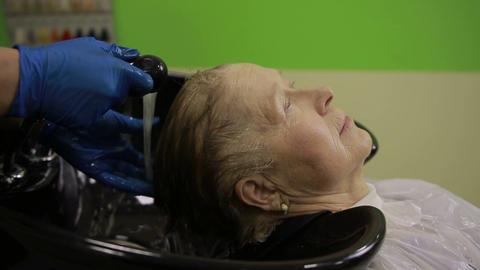 Senior woman enjoying hair washing in salon Live Action