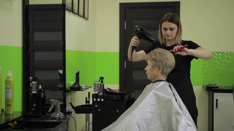 Hairdresser drying woman's hair using hair dryer Footage