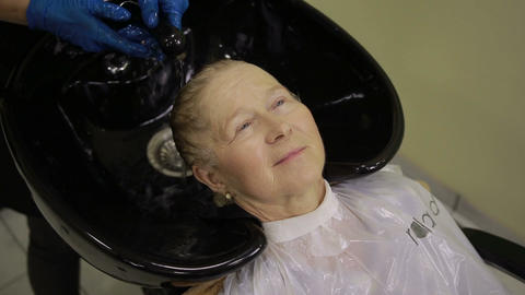 Hairdresser washing hair to female customer Live Action