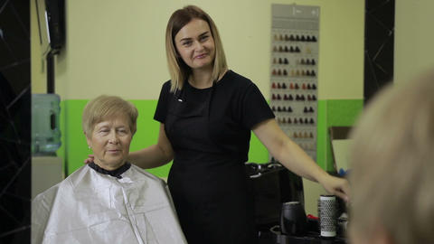 Happy woman looking at her haircut in hair salon Live Action