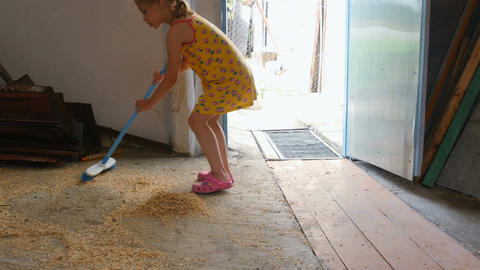 Little girl sweeps the sawdust into a heap Footage