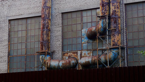 Building with rusty pipes stands behind a fence Footage