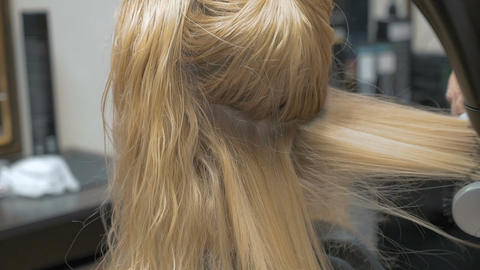 A stylist barber combs her hair to a blonde woman using a hairdryer Footage
